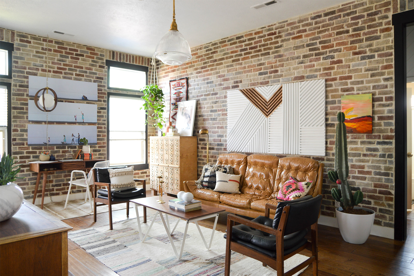 Bright living room with brick walls and wood floors