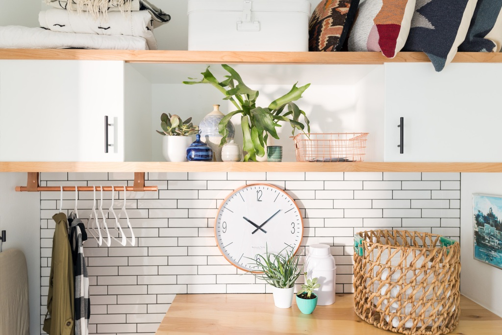 Updated laundry room with white subway tile and a clock