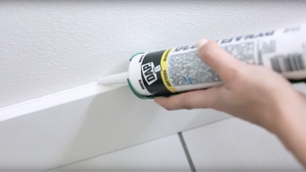 Woman applying caulk to a wall