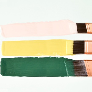 Three paintbrushes with green, yellow, and pink paint
