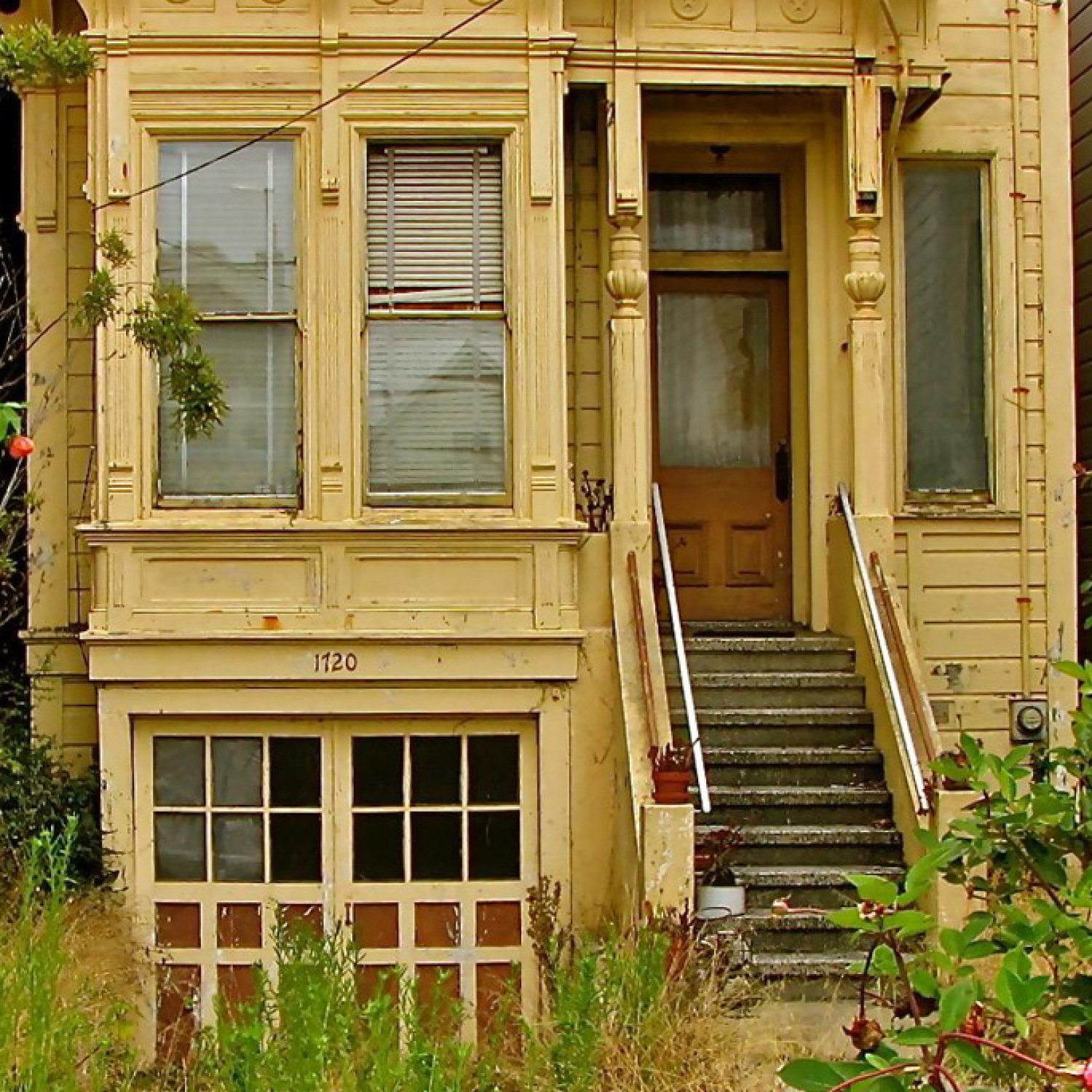 Dilapidated home exterior with overgrown weeds
