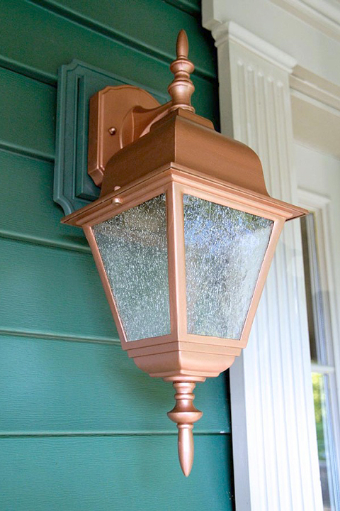 Green house siding with new copper painted porch light