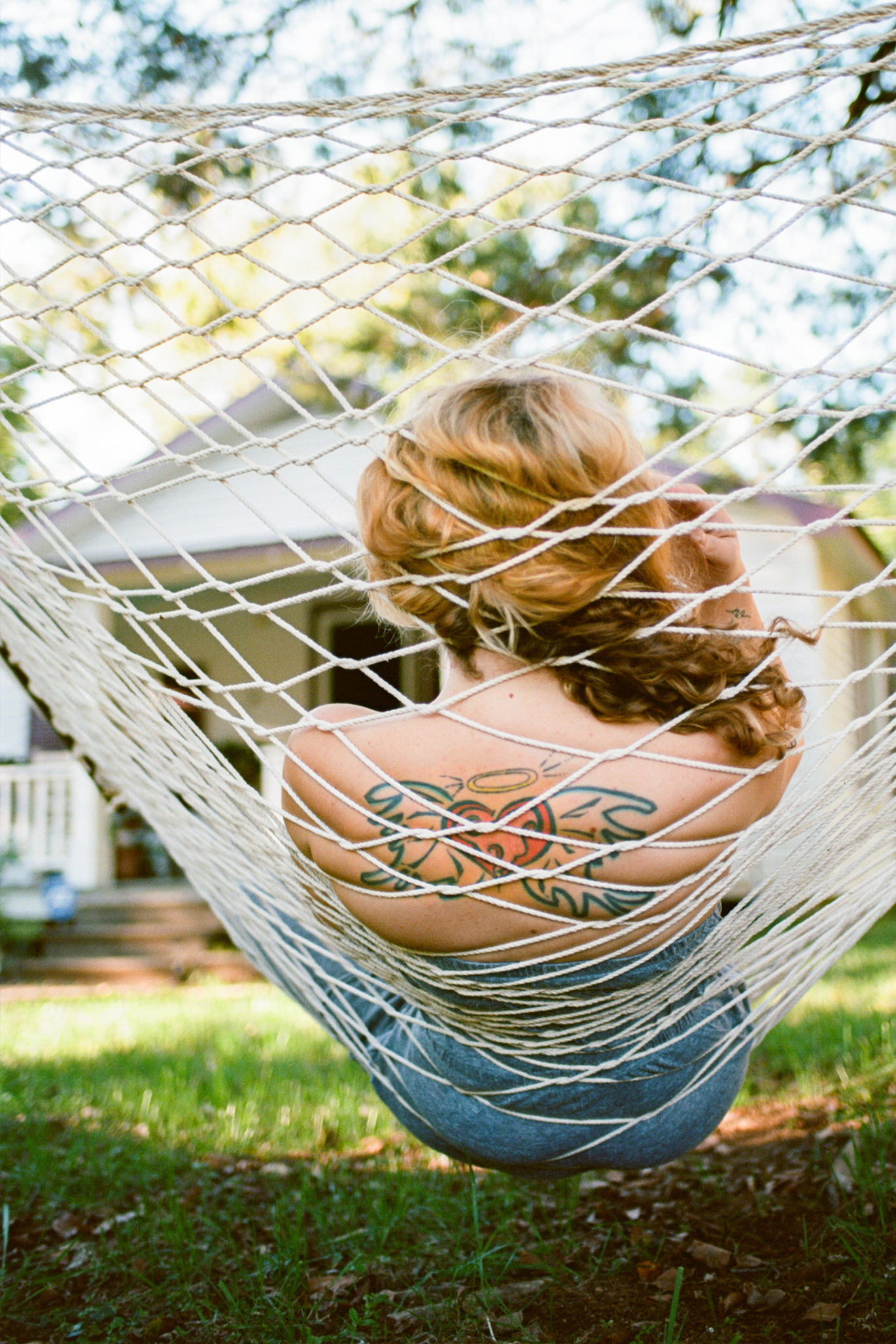 Woman with tattoo relaxing in hammock