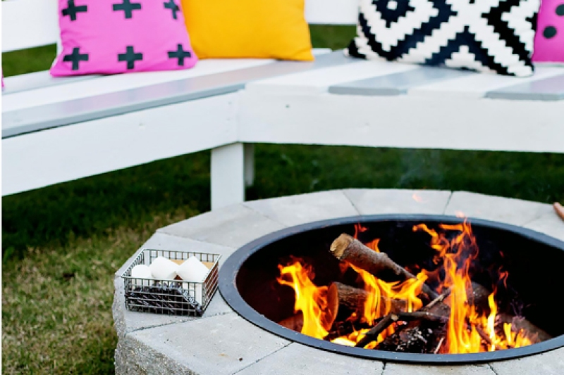 A firepit with a white bench with accent pillows