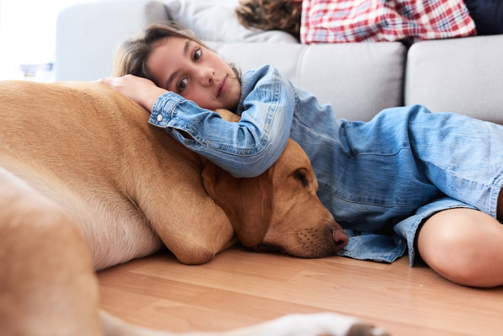 A young girl is hugging her dog on the wood floor