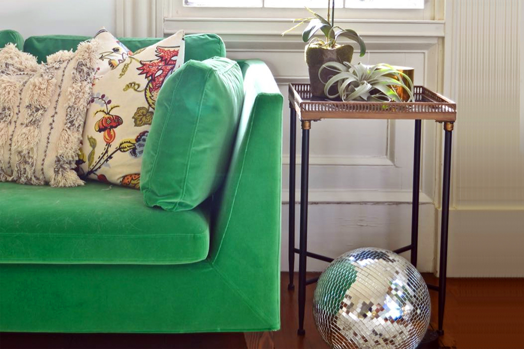 Green velvet couch in a home living room