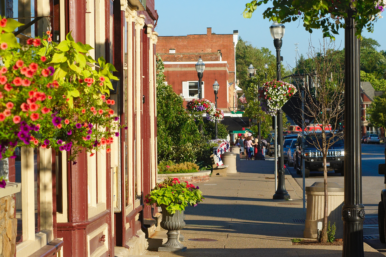 Bright sidewalk with store fronts and hanging flower baskets
