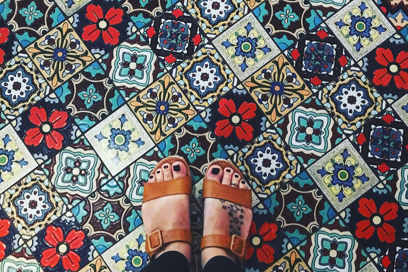 A mosaic tile floor with feet in sandals