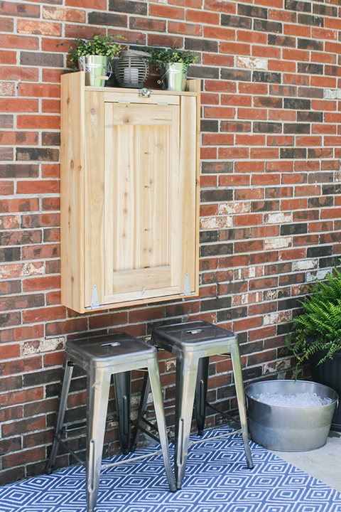 Closed wood cabinet on a brick wall with gray stools