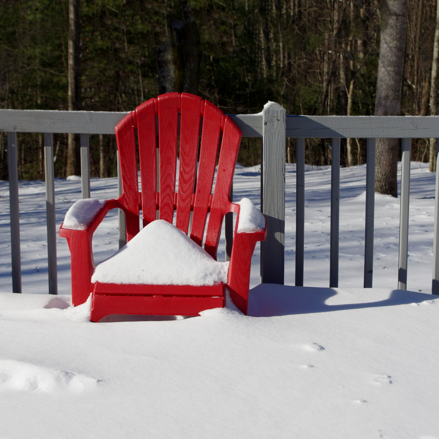 A red chair covered in snow