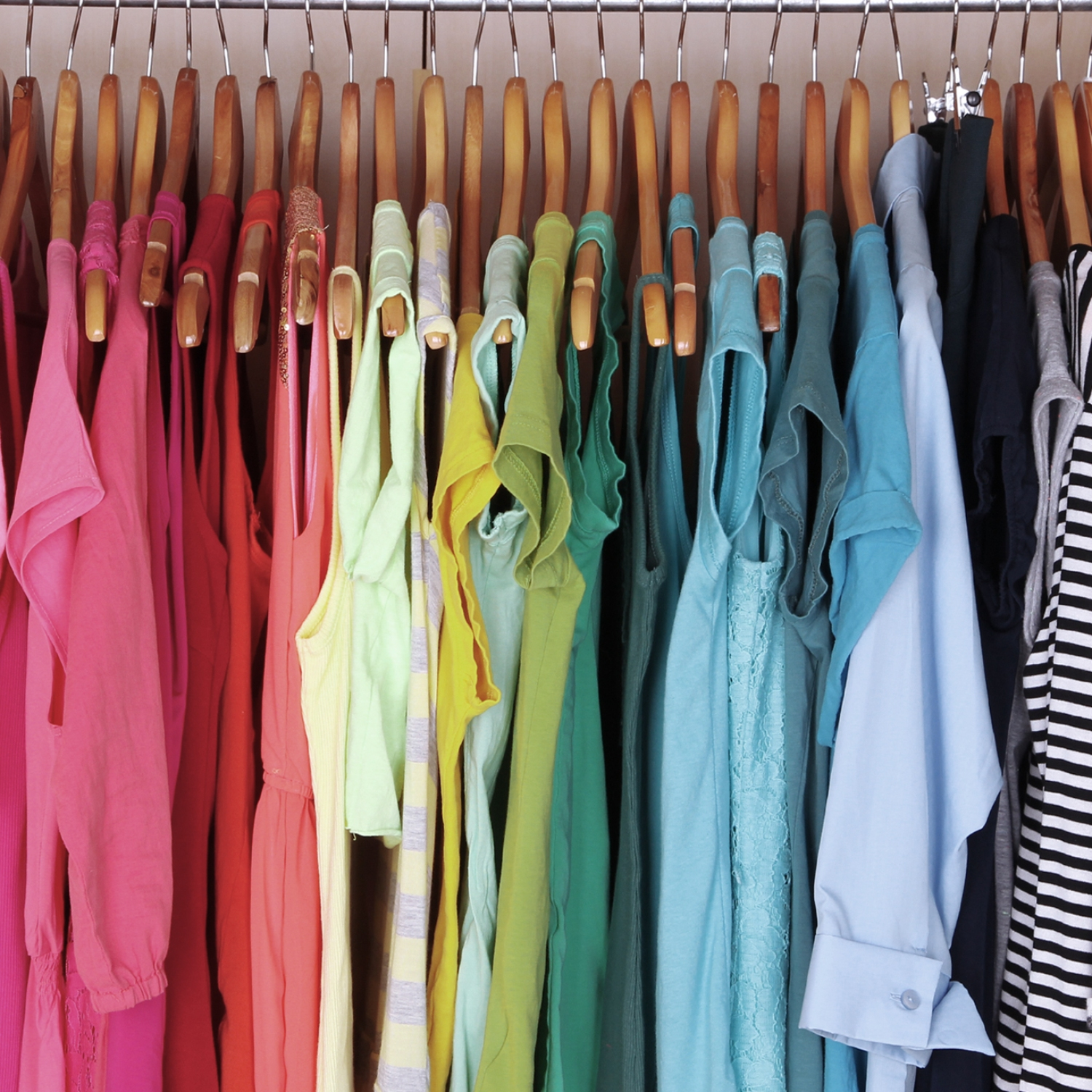 Rainbow organized clothes in a closet