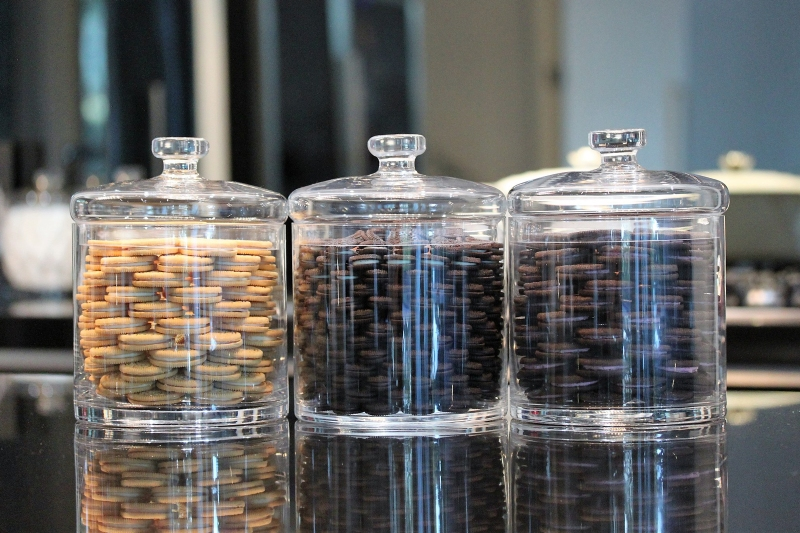 Three clear glass canisters filled with sandwich cookies