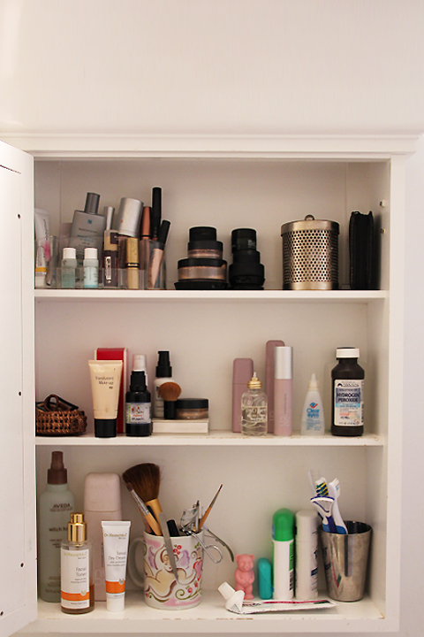 A dim medicine cabinet filled with toiletries