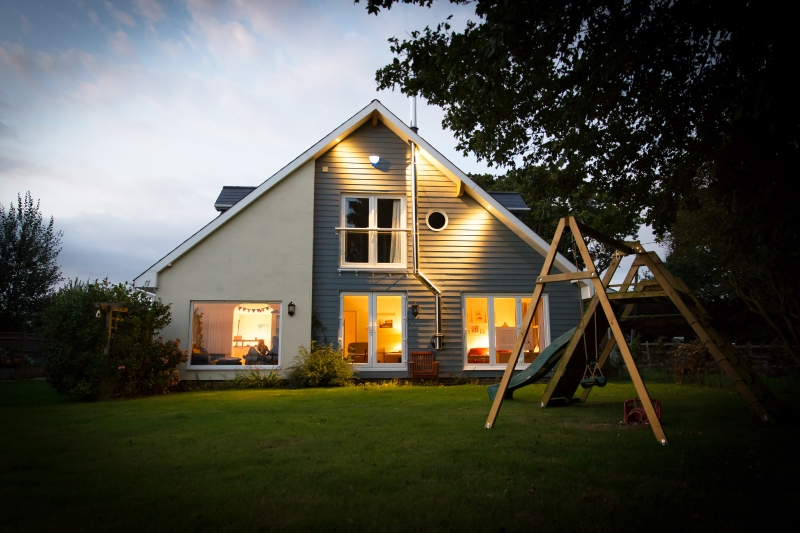 House with swing set illuminated at night | Prevent Burglary