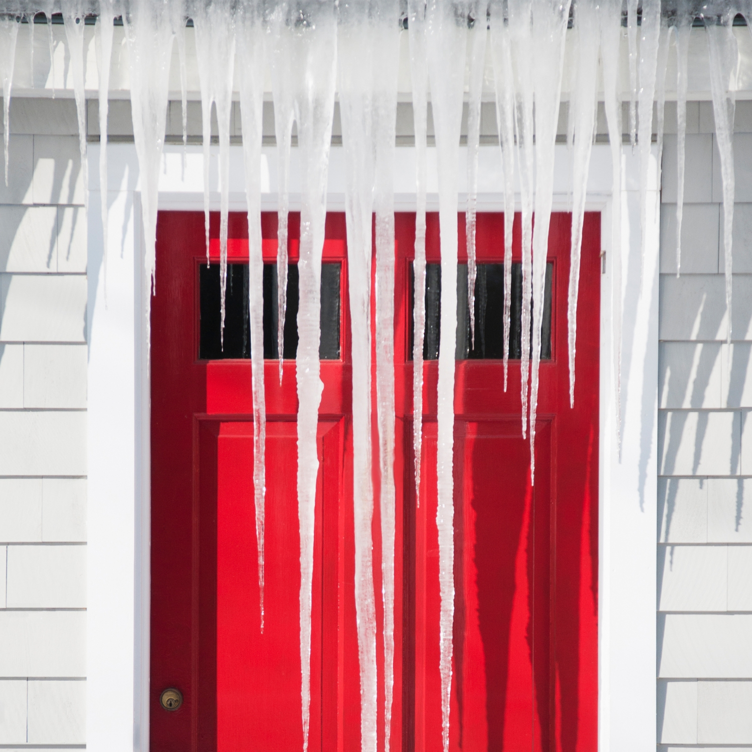 Icicles covering front of house in winter