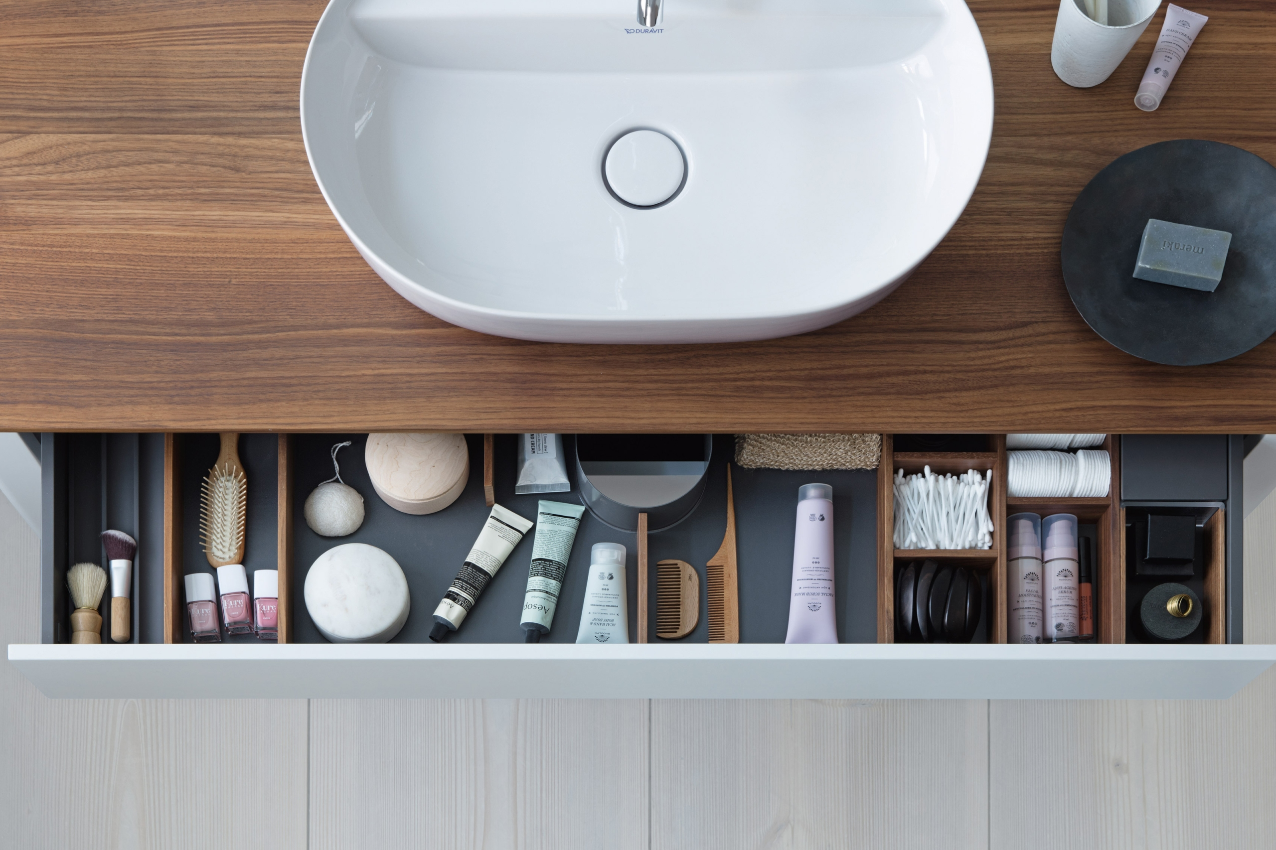 An overhead view of a bathroom sink and open drawer