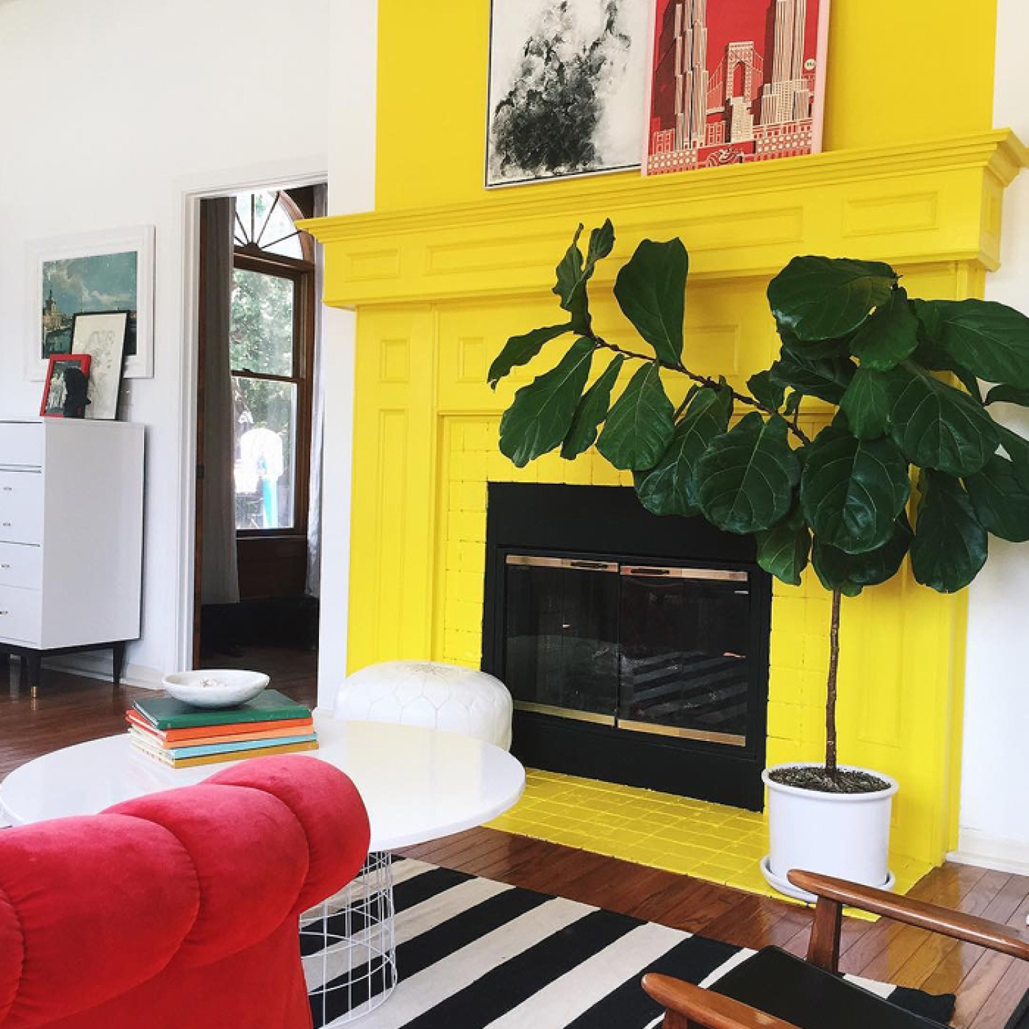 A bright yellow painted fireplace with fiddle leaf fig