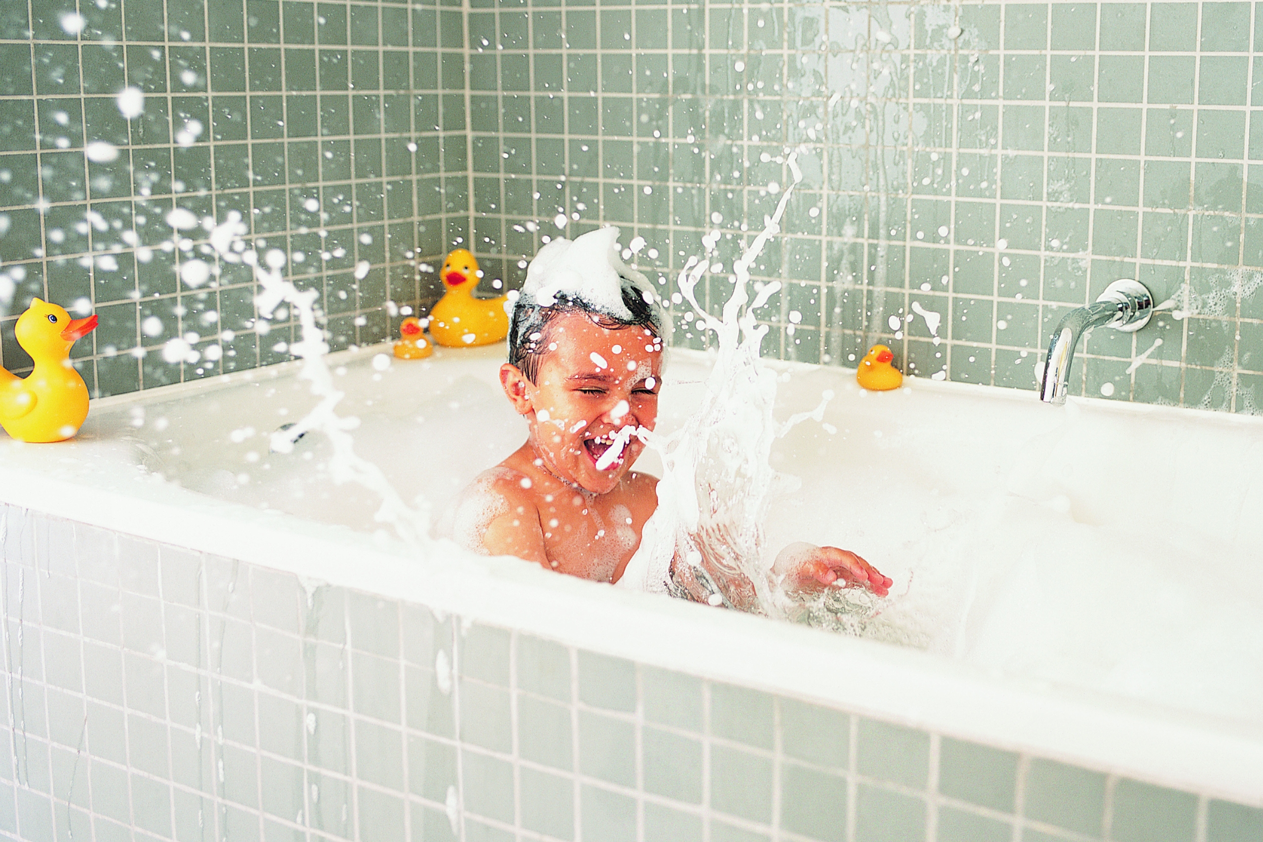 A young boy in a bath tub surrounded with bubbles & ducks