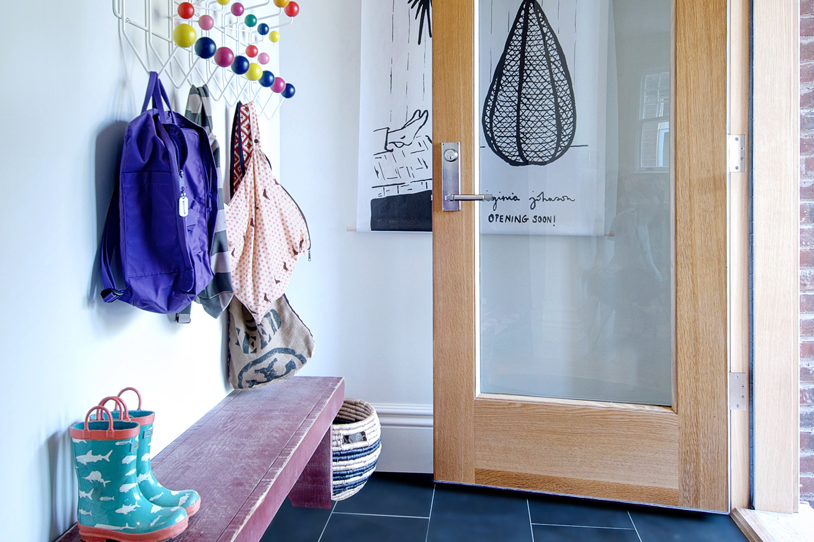 A bright entryway with colorful coat hanger and backpacks