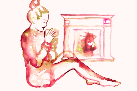 Woman staying warm by her home fireplace