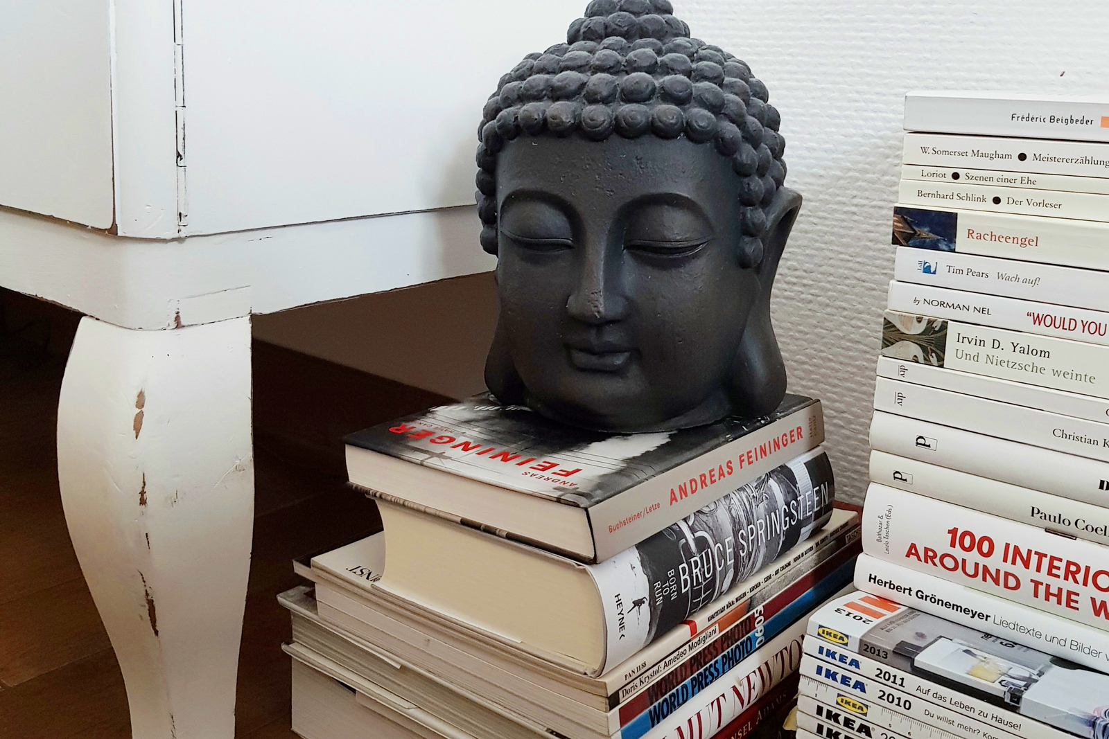 A gray buddha statue on a stack of white books, catalogs