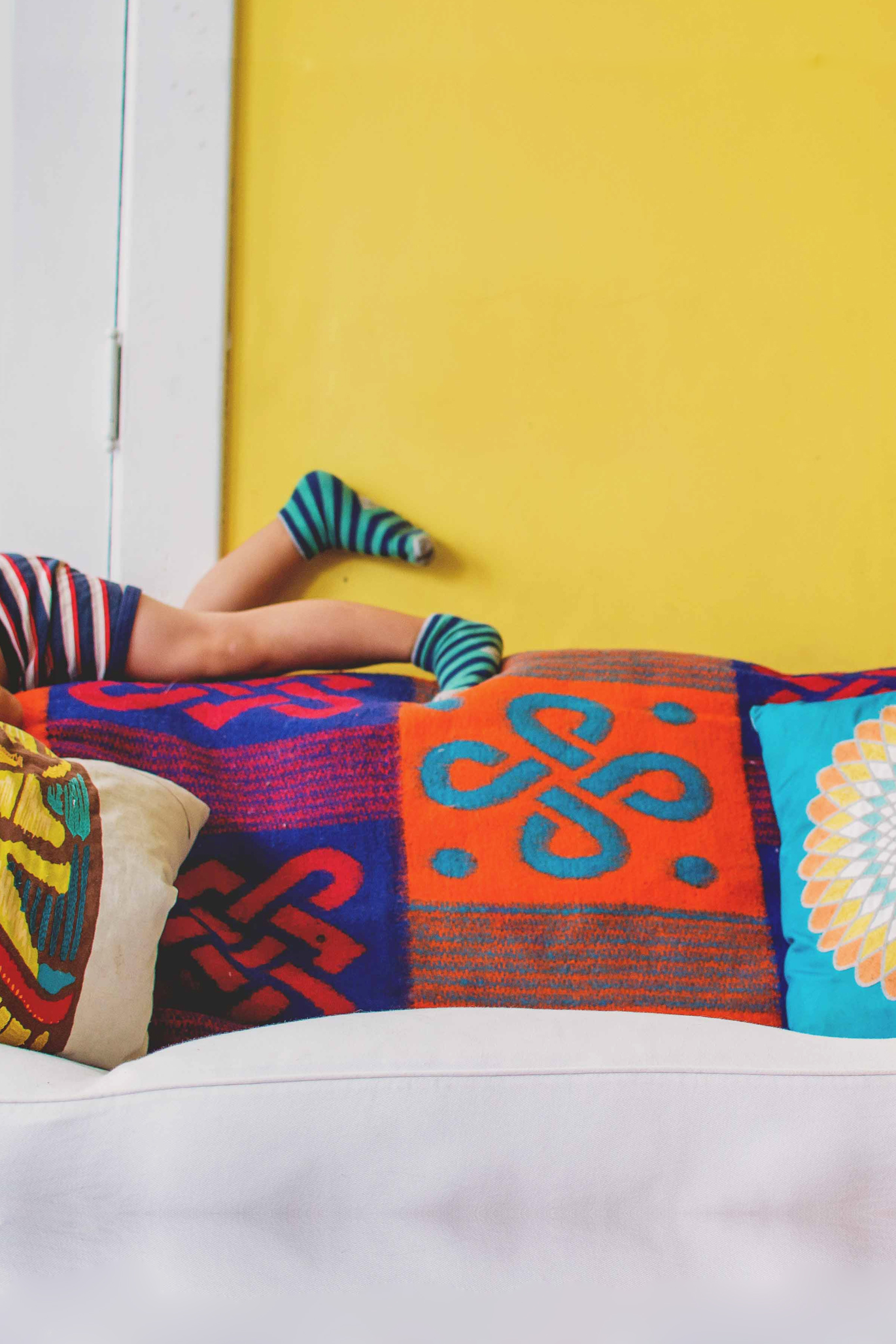 Eclectic home with colorful yellow wall and fun throw pillow