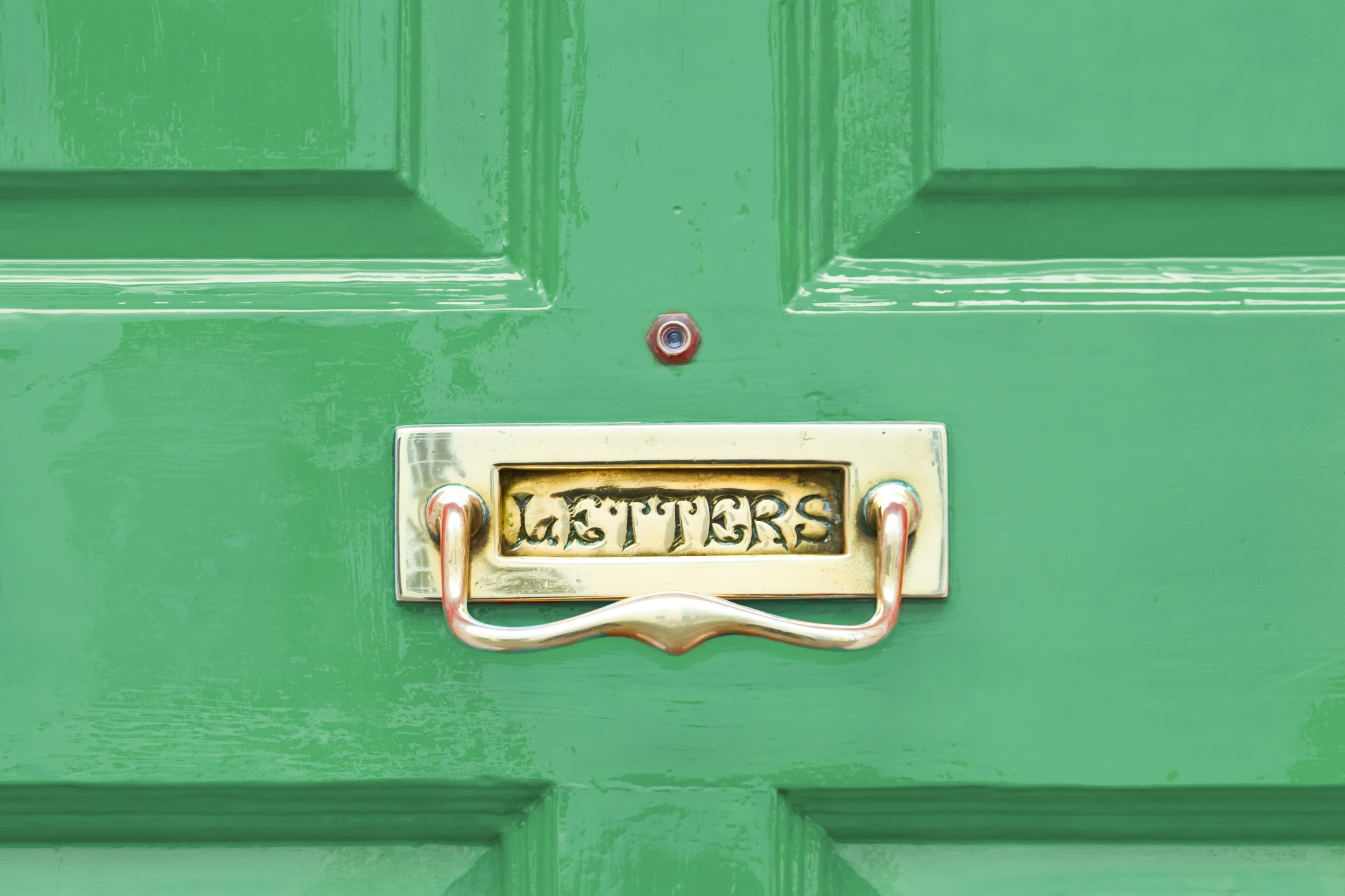 Bright green wood entry door with built-in mailbox