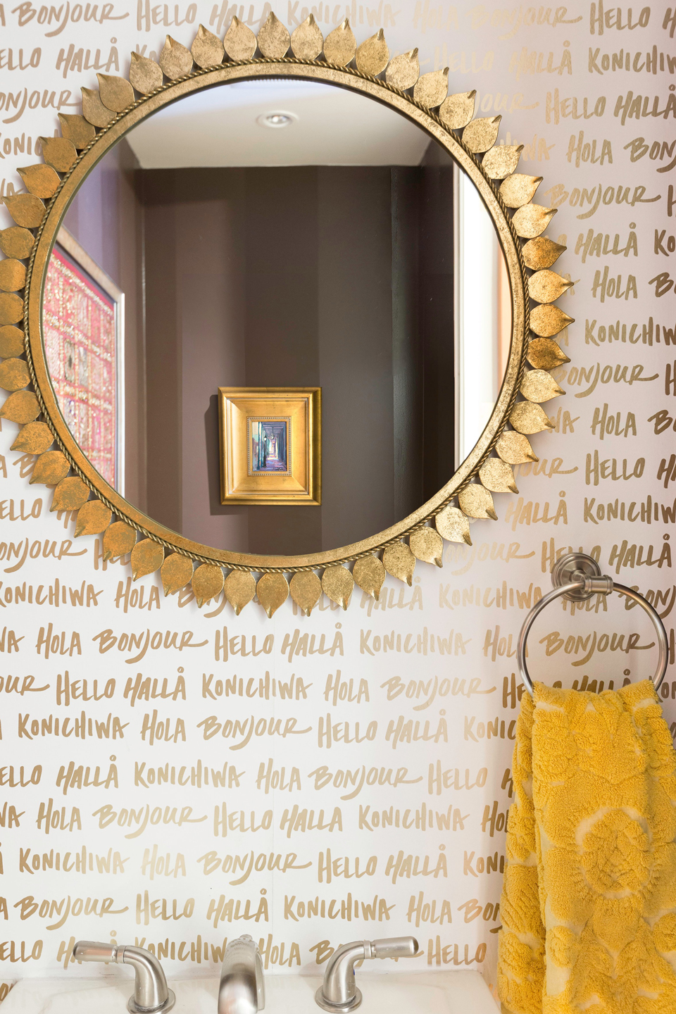 White wallpaper with gold lettering in a bathroom