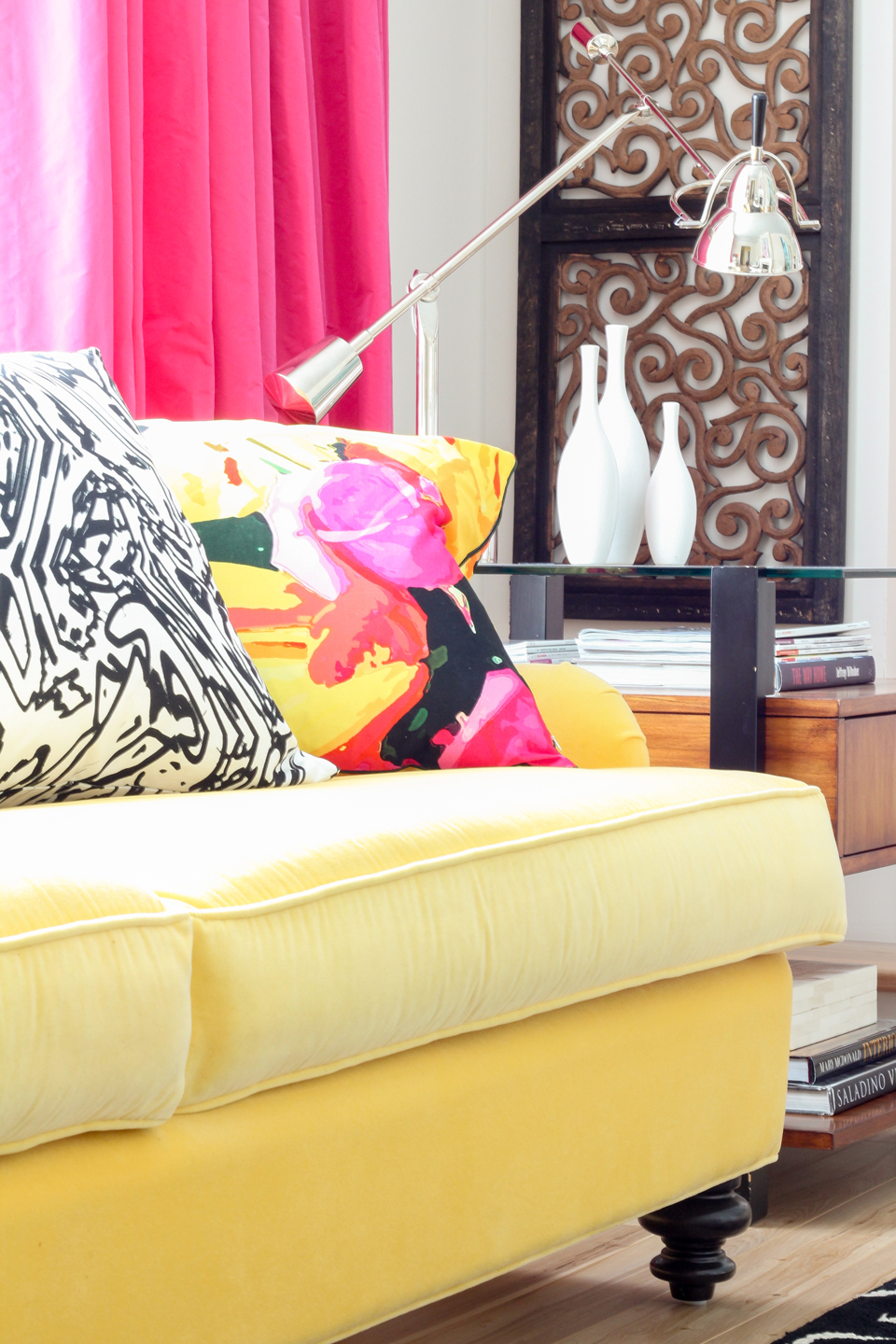 A close-up of a yellow couch, pink curtains, & floral pillow