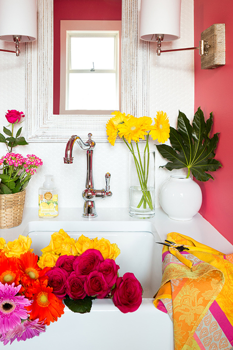 A hot pink painted bathroom with flowers in the sink
