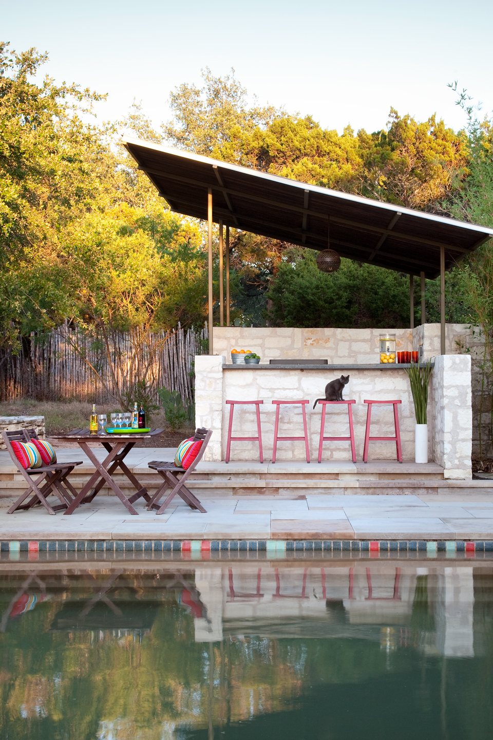 An after image of a midcentury pool with bar and stools