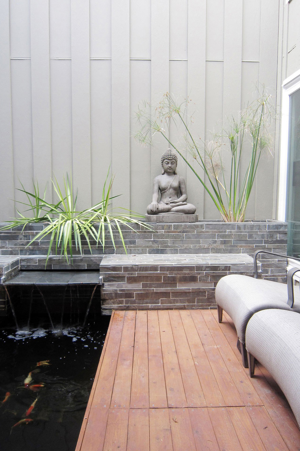 An after image of a small backyard with a fountain