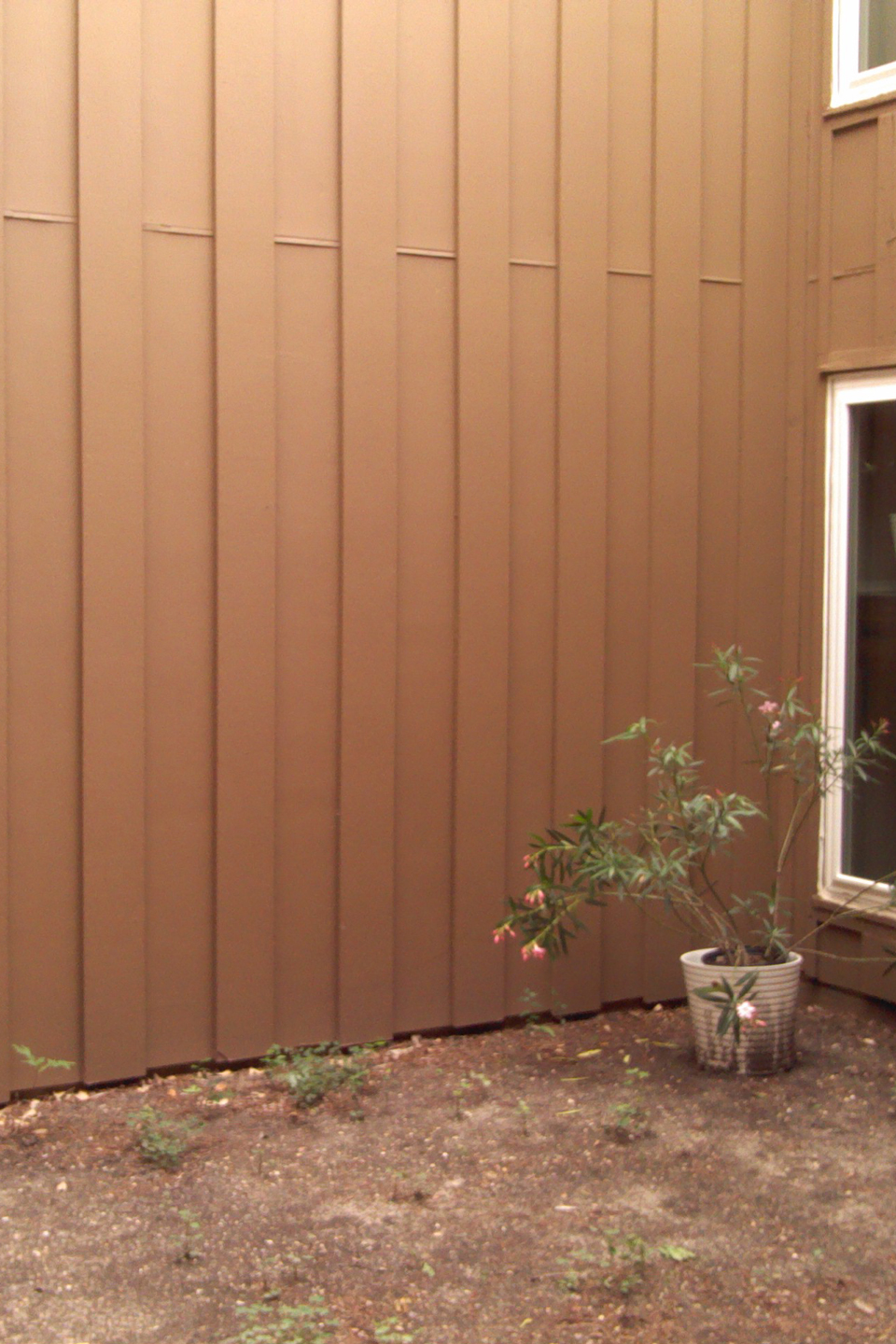 A before image of a small yard with a dirt patch