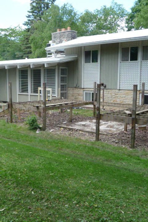 A before image of a front yard with wood risers for deck