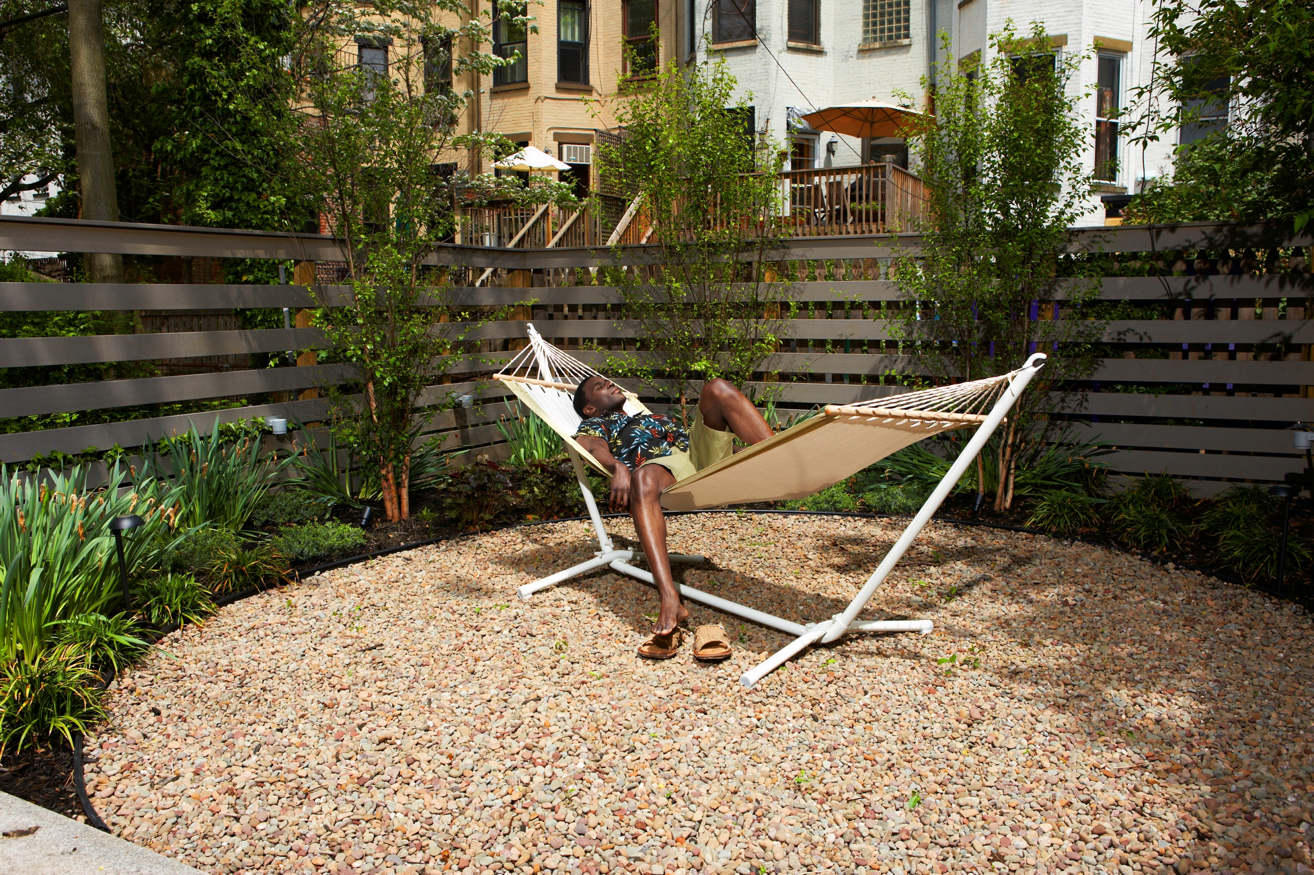Man relaxing on a hammock in an urban back yard