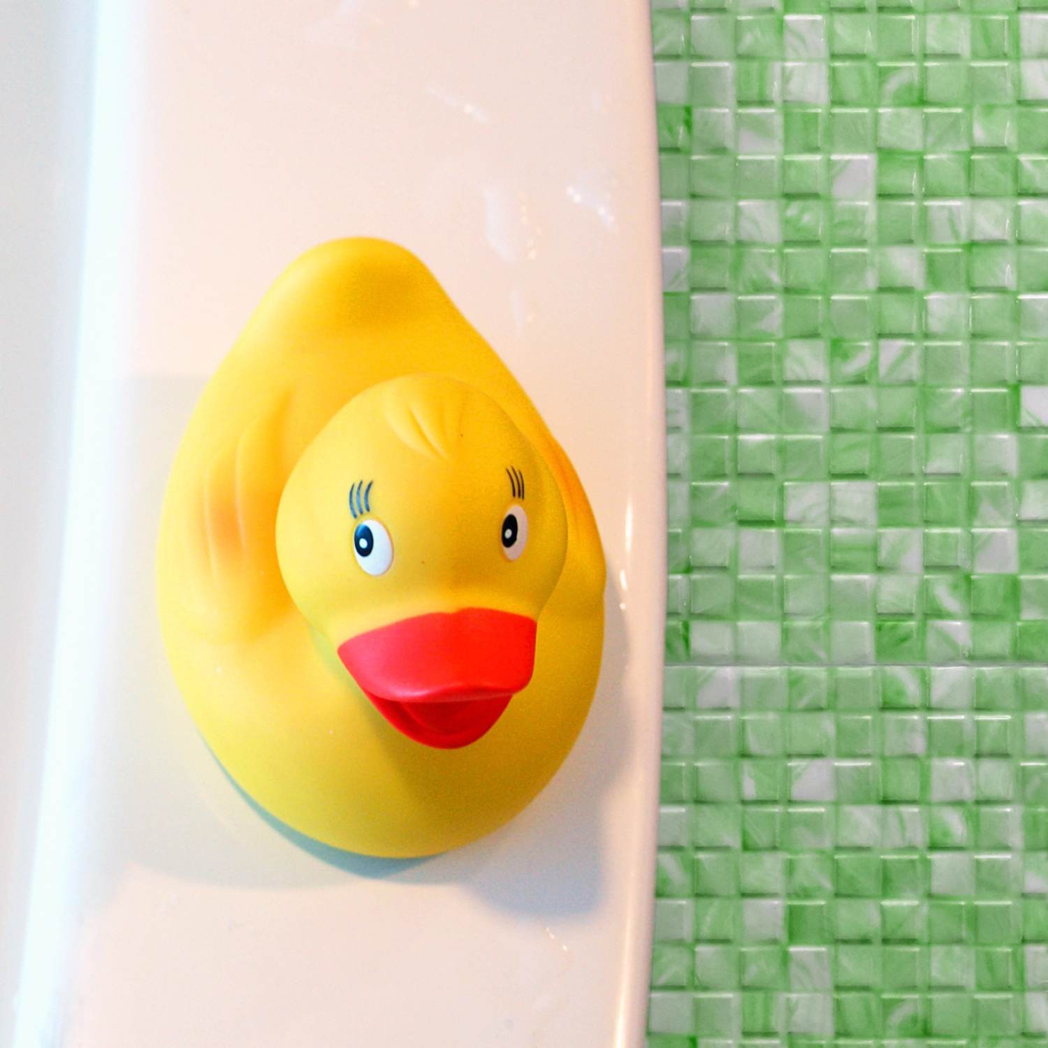 Rubber ducky on a tub in a bathroom