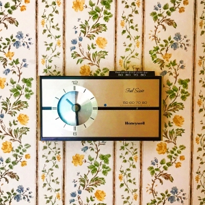 Vintage wallpaper with outdated thermostat in a home
