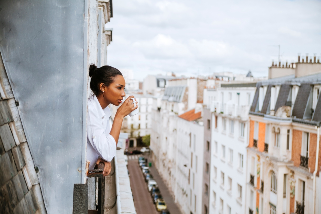French woman drinking coffee looking out of her window