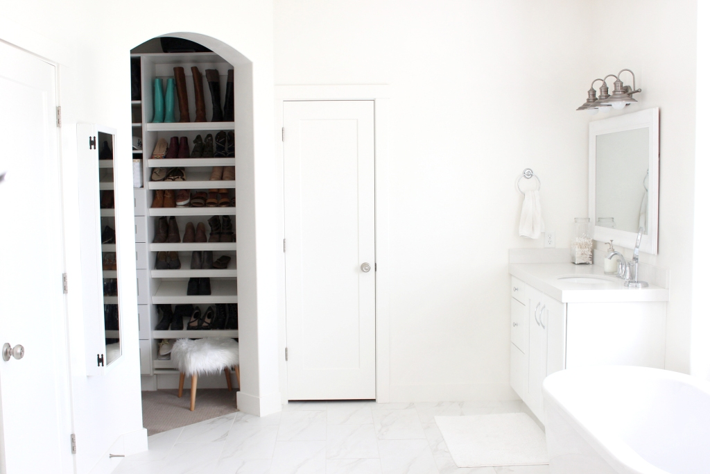 All white bathroom with glimpse of a shoe closet
