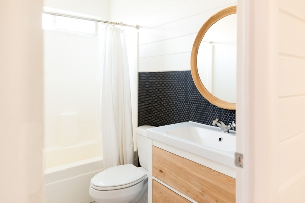 A white bathroom with black tile and natural wood accents