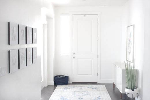 White entryway with pictures along one wall and white rug
