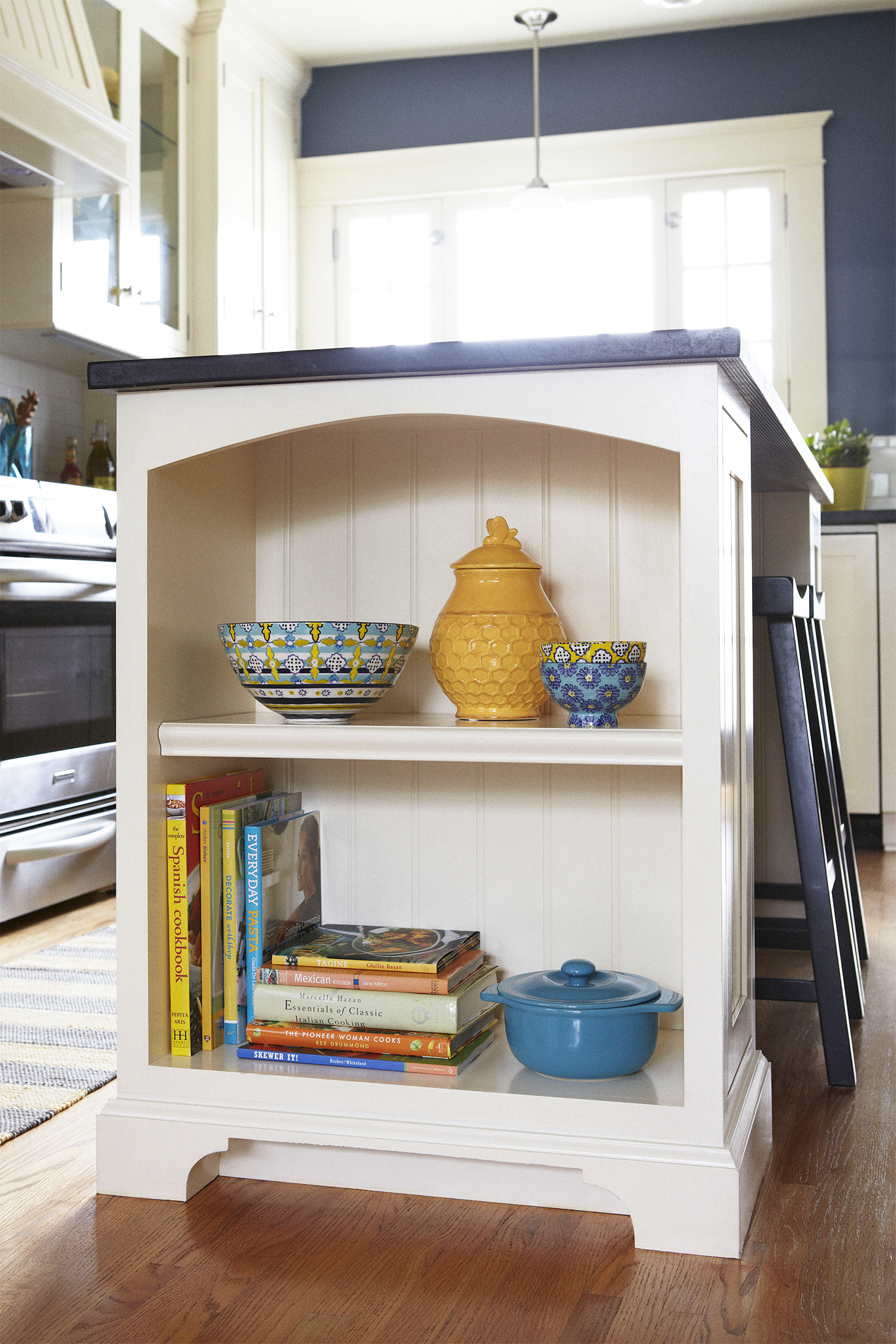 Organize shelf in kitchen with yellow pots and cookbooks