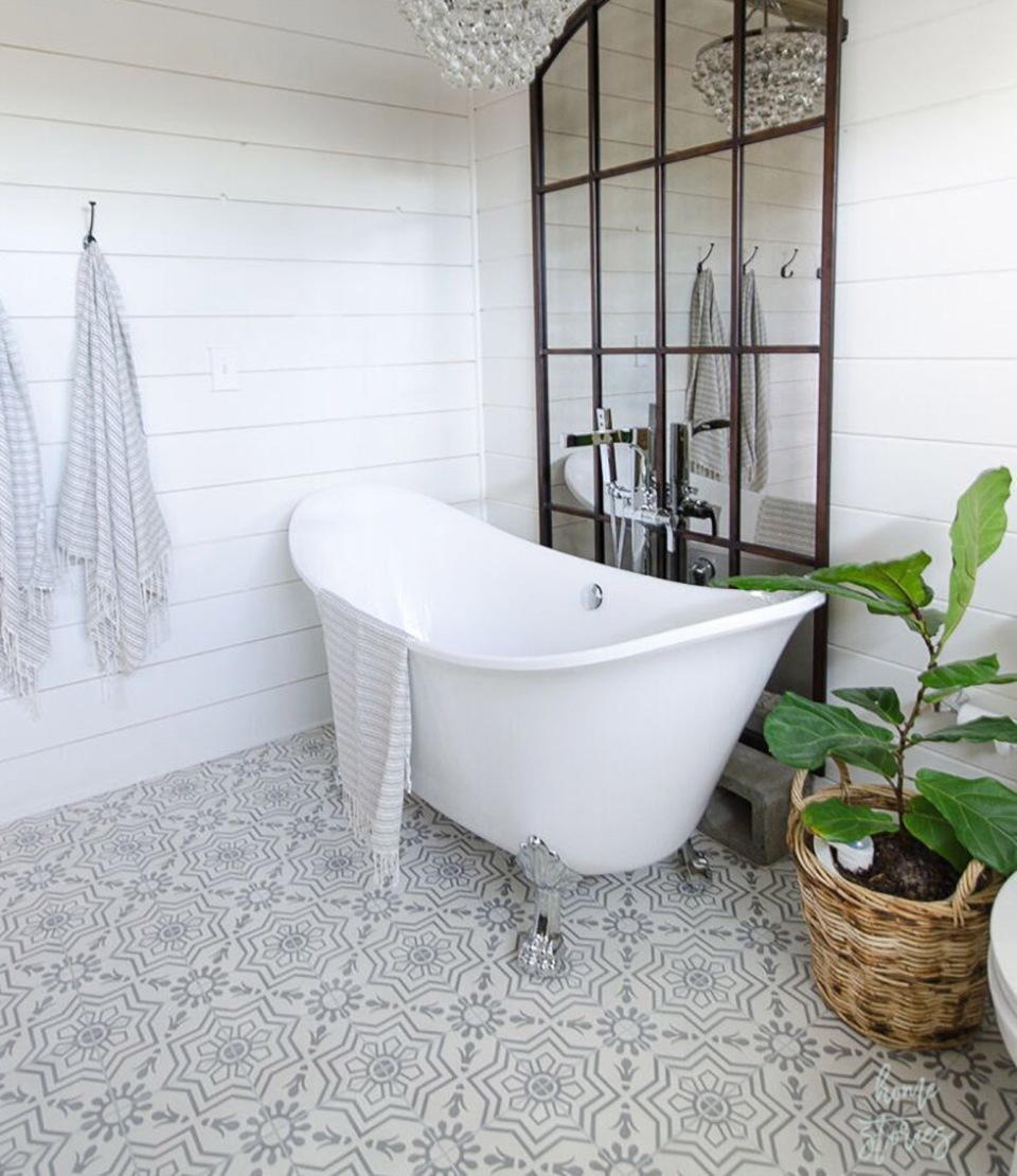 Patterned tile in bathroom with white tub and chandelier