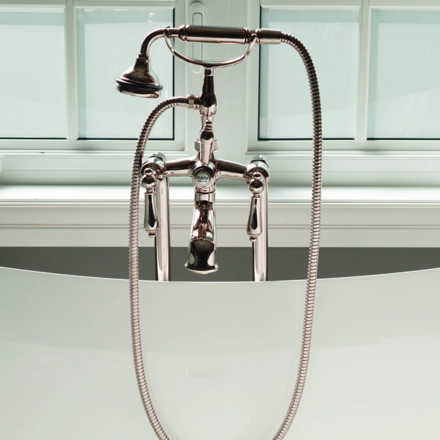Close up of removable shower head resting on cradle in tub
