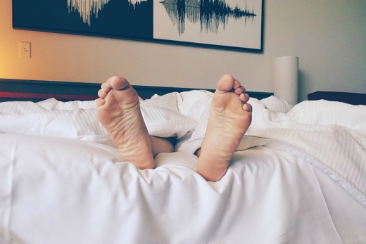Pair of feet sticking out from white bedsheets