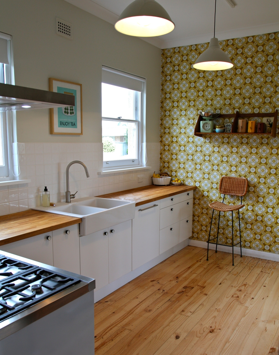Remodeled kitchen with white cabinets, patterned accent wall
