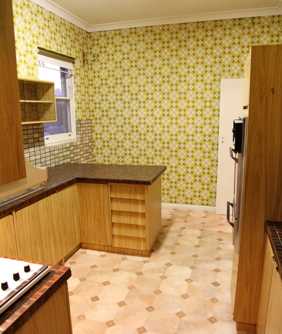 Seventies-style kitchen with brown cabinets, patterned walls