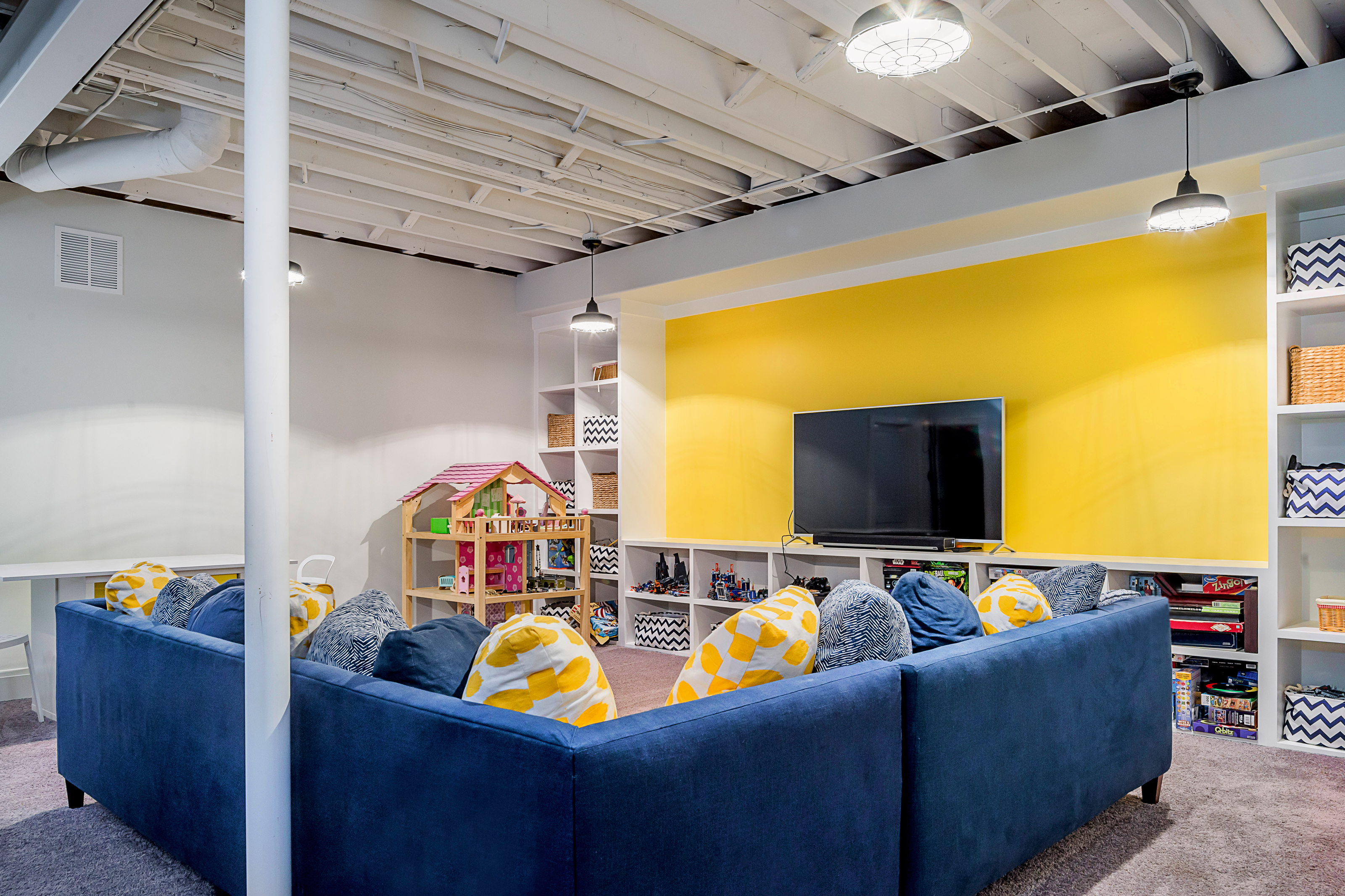 Blue and yellow basement with built-in shelves, open ceiling
