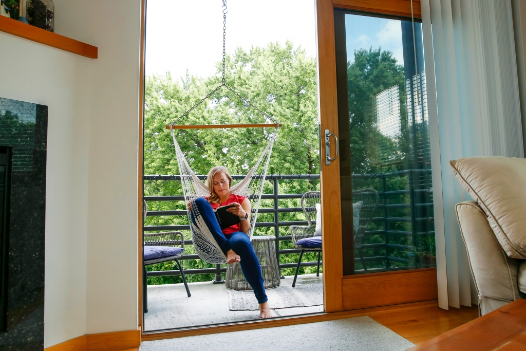 Andrea Lawson in a chair hammock enjoying her condo balcony