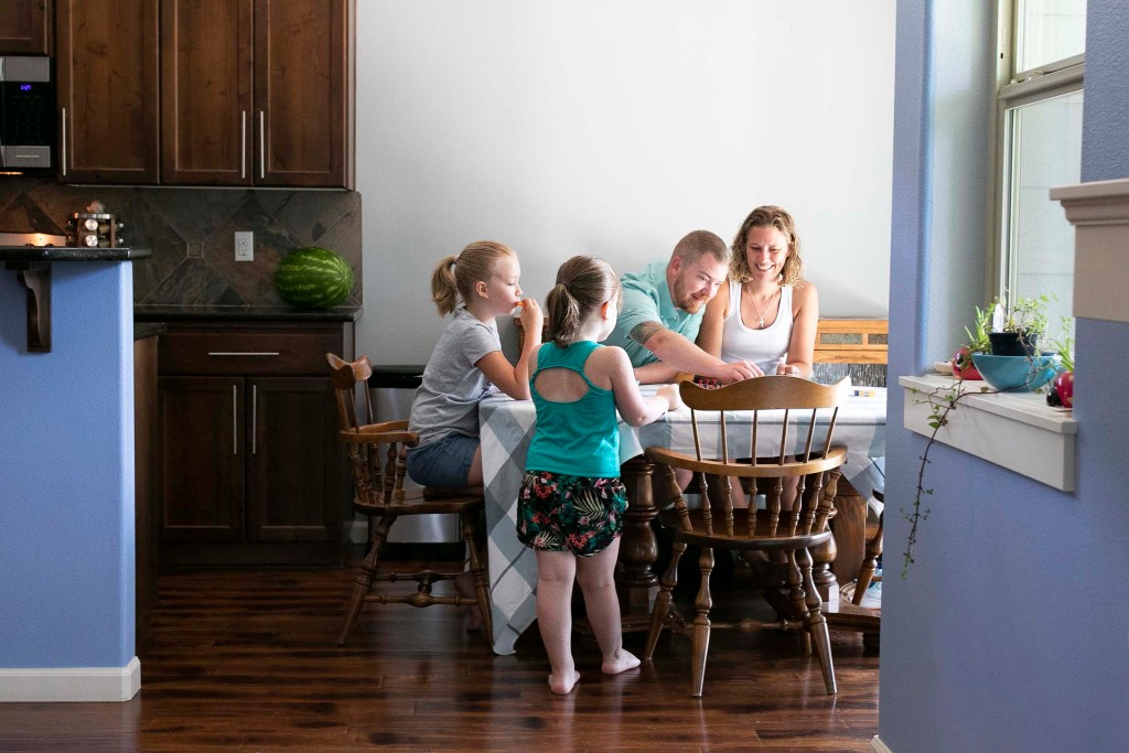 Mark and Jena Boomhower with their daughters at a table.
